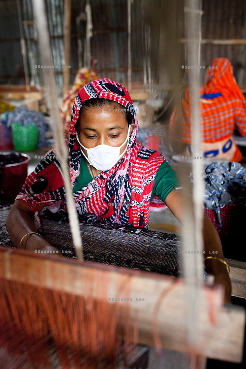 Nuna Begum (in red/green sari), works on a rug at the Mornia Kik Rug Factory in Doani Villlage, Haragach Upazila, Rangpur, Bangladesh on 19th September 2011 where she works alongside 25 rural village women making rugs for German textile discounter Kik. Over 400 women have been economically empowered through the CARE Bangladesh WONDER Project that was completed recently. The WONDER Project's goals were to create sustainable income and employment opportunities for extremely poor women by training them in rug production for export. The women now earn about 4000 Bangladeshi Taka per month. The WONDER Project has now moved into a new phase that focusses on general healthcare, workplace safety and nutritional training and awareness programs. Photo by Suzanne Lee for The Guardian