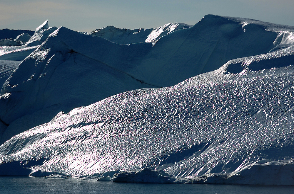 """The Ilulissat Icefjord, a UNESCO World Heritage Site, is located on the west coast of Greenland, 250 km north of the Arctic Circle. It is the sea mouth of Sermeq Kujalleq, one of the few and most productive glaciers through which the Greenland ice cap reaches the sea. Pieces of ice several cubic kilometres in size break offs and travels the Arctic sea, Greenland. Greenland (Greenlandic: Kalaallit Nunaat, meaning """"Land of the Kalaallit (Greenlanders) is a self-governing Danish province located between the Arctic and Atlantic Ocean. A recent study by researchers from NASA's Goddard Space Flight Center shows that Greenland's ice sheet, about 8% of the Earth's grounded ice, is losing ice mass."""