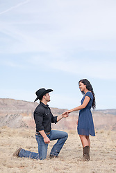 cowboy on one knee proposing to a a girl outdoors