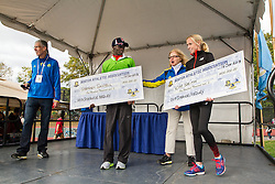 Boston Athletic Association Half Marathon; Distance Medley winners Stephen Sambu, Kim Smith on podium receiving checks for $100,000 each