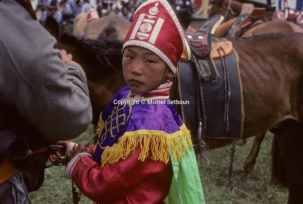 Mongolia. Naadam of childrens  Nangadel       /  Jeune moine à cheval.(Nangadel, sum de Qudjirt, aymag de Ovorqangay : Mongolie) Paré de son costume de religieux (deel avec manches en sabot, et couvre-chef de couleur jaune à rebord rouge) ce tout jeune apprenti-moine en vacances est venu à cheval assister au Naadam de courses de chevaux. Les familles sont généralement fières de mettre leur fils dans les ordres religieux, car celui-ci sera instruit et peut-être même savant, comme dans l'ancienne société.   /      51