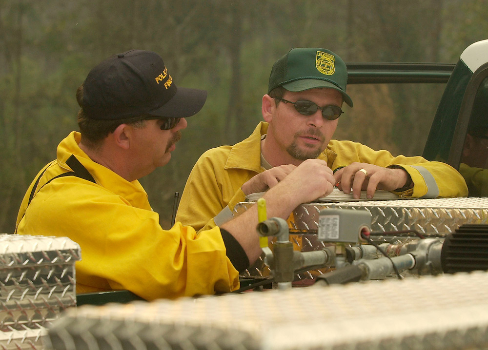 Division of Forestry Forest Area Supervisor Chris Worrell, right, looks over some maps of the area with Polk County, Fla. fire department Captain John Phillips while watching over a backfire that was set to help control an approximately 200 acres wildfire in Polk County, Fla. on Friday, Jan., 26, 2000 near Polk City, Fla. (AP Photo/Scott Audette)