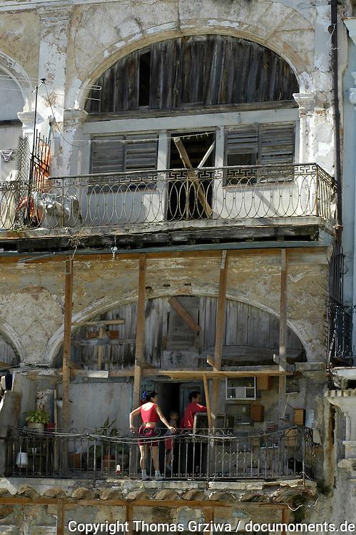 Wohnen auf Kuba: Bewohner eines verfallenen Wohnhauses in der Altstadt von Havanna stehen auf dem Balkon, der mit St?tzbalken notd?rftig stabilisiert wird.