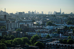 © Licensed to London News Pictures. 14/06/2017. London, UK. A view over the rooftops of west London showing Notting Hill in the foreground and the London city landscape in the background, including The Shard, Canary Wharf and the London Eye. Photo credit: Ben Cawthra/LNP