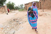 Habsita Moussa, 30, carries her son Abdelnassir Haroun, 6 mo., as she walks back home from a meeting at CELIAF in Mongo, Guera province, Chad on Wednesday October 17, 2012.