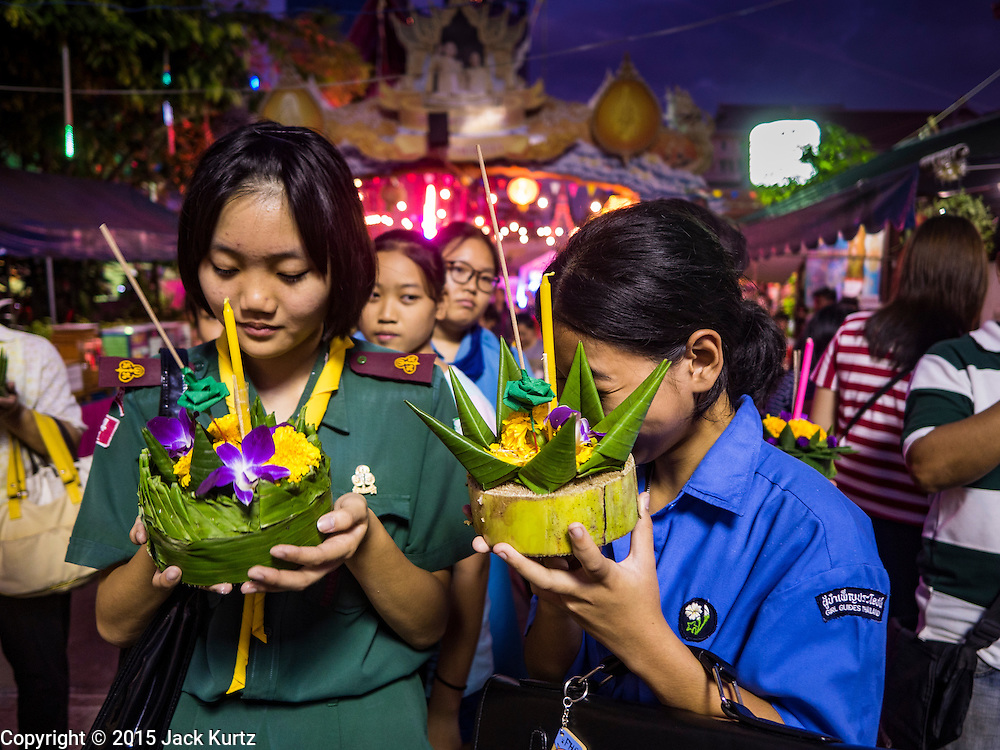 """25 NOVEMBER 2015 - BANGKOK, THAILAND:   Thai """"Girl Guides"""" (Girl Scouts in the US) prays before floating their krathong in the Chao Phraya River during Loy Krathong at Wat Yannawa in Bangkok. Loy Krathong takes place on the evening of the full moon of the 12th month in the traditional Thai lunar calendar. In the western calendar this usually falls in November. Loy means 'to float', while krathong refers to the usually lotus-shaped container which floats on the water. Traditional krathongs are made of the layers of the trunk of a banana tree or a spider lily plant. Now, many people use krathongs of baked bread which disintegrate in the water and feed the fish. A krathong is decorated with elaborately folded banana leaves, incense sticks, and a candle. A small coin is sometimes included as an offering to the river spirits. On the night of the full moon, Thais launch their krathong on a river, canal or a pond, making a wish as they do so.    PHOTO BY JACK KURTZ"""