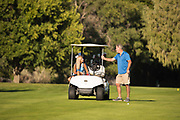 Senior couple golfing in cart during evening in the canyon at the public course, Clear Lakes Country Club in Buhl, Idaho. MR