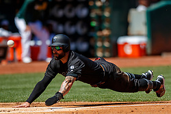 OAKLAND, CA - AUGUST 25: Kevin Pillar #1 of the San Francisco Giants dives into home plate to score a run against the Oakland Athletics during the second inning at the RingCentral Coliseum on August 25, 2019 in Oakland, California. The San Francisco Giants defeated the Oakland Athletics 5-4. Teams are wearing special color schemed uniforms with players choosing nicknames to display for Players' Weekend. (Photo by Jason O. Watson/Getty Images) *** Local Caption *** Kevin Pillar