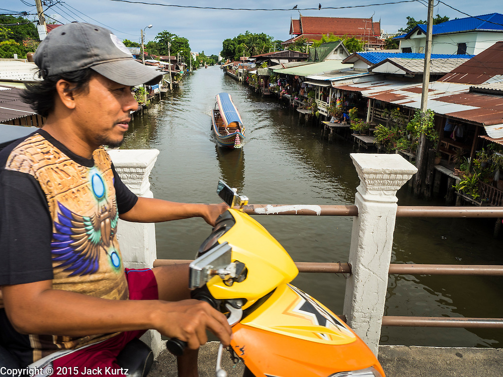 27 JUNE 2015 - BANGKOK, THAILAND:   A motorcycle on a bridge while boats pass on Khlong Bang Luang in the Bang Luang neighborhood of the Thonburi section of Bangkok. The Bang Luang neighborhood lines Khlong (Canal) Bang Luang in the Thonburi section of Bangkok on the west side of Chao Phraya River. It was established in the late 18th Century by King Taksin the Great after the Burmese sacked the Siamese capital of Ayutthaya. The neighborhood, like most of Thonburi, is relatively undeveloped and still criss crossed by the canals which once made Bangkok famous. It's now a popular day trip from central Bangkok and offers a glimpse into what the city used to be like.       PHOTO BY JACK KURTZ