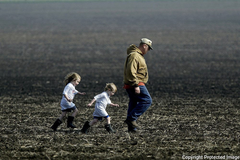 LITTLE SPROUTS - Sisters Tiffany, 5, (left) and Alyssa, 4, Johnson stride behind their uncle, Dustin Carlson, as he inspects the field he planted the evening before.  Because of heavy spring rains, farmers have been delayed in planting their crops of corn and soybeans.  Carlson, from Odebolt, Ia.,  was worried that certain parts of the field didn't get covered with seed when his planter got stuck in some wet spots. PHOTOGRAPH BY DAVID PETERSON -   Photo by David Peterson