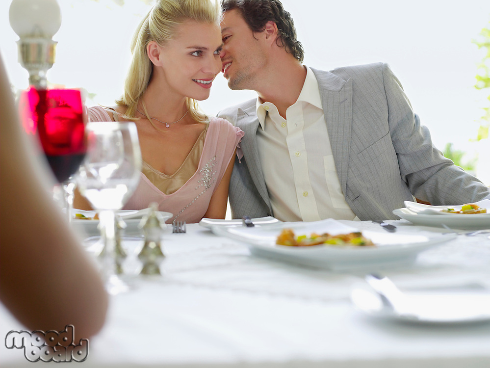 Formally dressed young Couple Whispering at Dinner table