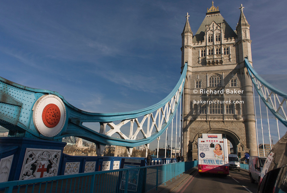 Bus rear advertising for Abba's West End musical Mamma Mia as it drives over Tower Bridge and central London streets.