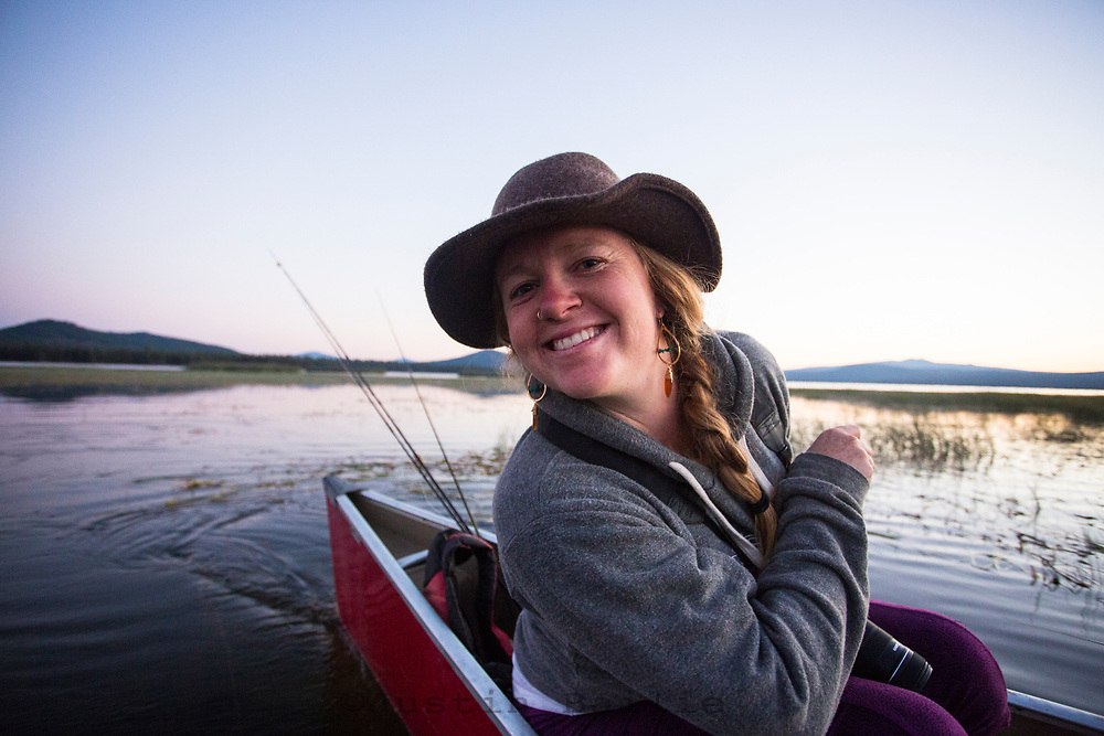 Young woman canoeing and fly fishing on Crane Prairie Reservoir, Oregon.