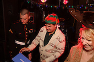 (from right) Rhonda and Rusty Kuriger of Cedarville deposit their 'toy admission' into the collection box at the Dublin Pub during the Santa Claus Pub Crawl through the Oregon District in downtown Dayton, Saturday, December 11, 2010.