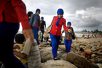 Acehnese women walk along a new jetty created by the tsunami, in Ulele Beach, outside of Banda Aceh, Indonesia, Sunday, Nov. 8, 2009. Most families head to the beaches on Sundays. On Dec. 26, 2004, a 9.0 magnitude earthquake triggered a massive tsunami that killed 226,000 people throughout several countries. In Aceh, the death toll alone was 166,000.