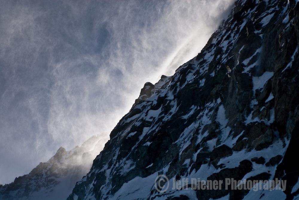 Spindrift cascades down a rock face along the Haute Route, Switzerland.