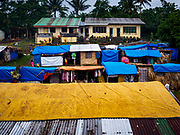 26 JANUARY 2018 - SANTO DOMINGO, ALBAY, PHILIPPINES: Thatched huts and tents for evacuees from the Mayon Volcano at Barangay Lidong shelter. The shelter is in school and all of the classrooms are already being used to house evacuees. Recent arrivals are living in tents and huts on the school grounds. The volcano was relatively quiet Friday, but the number of evacuees swelled to nearly 80,000 as people left the side of  the volcano in search of safety. There are nearly 12,000 evacuees in Santo Domingo, one of the communities most impacted by the volcano. The number of evacuees is impacting the availability of shelter space. Many people in Santo Domingo, on the north side of the volcano, are sleeping in huts made from bamboo and plastic sheeting. The Philippines is now preparing to house the volcano evacuees for up to three months.        PHOTO BY JACK KURTZ