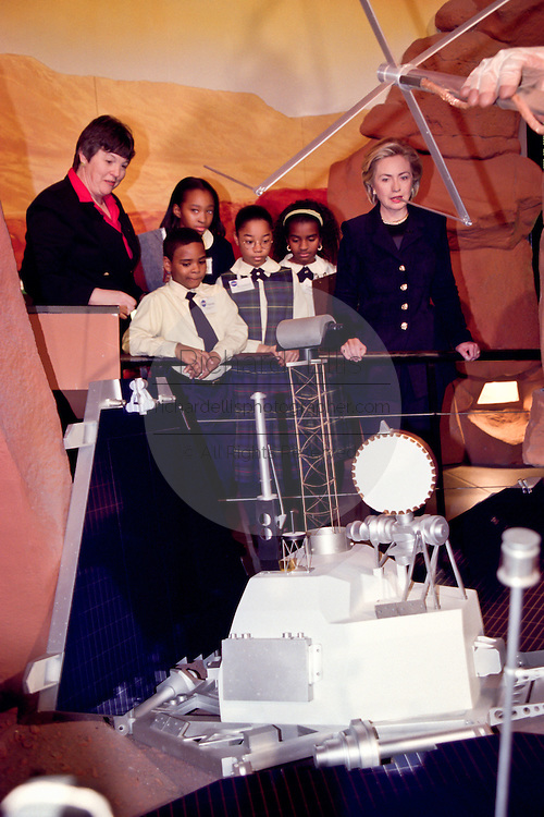 First lady Hillary Rodham Clinton listens to former Mars project manager Donna Shirley along with a group of local children as they tour the new ''Mars Millennium'' exhibition at the National Air & Space Museum January 14, 1999 in Washington, DC.