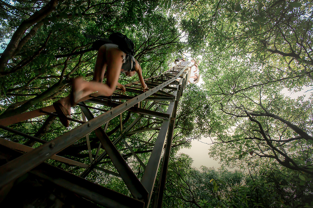 Woman climbs to observation point, the highest accessible location on Little Corn Island. Copyright 2017 Reid McNally.