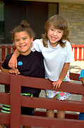 Friends age 5 with arms around shoulders at school.  St Paul Minnesota USA