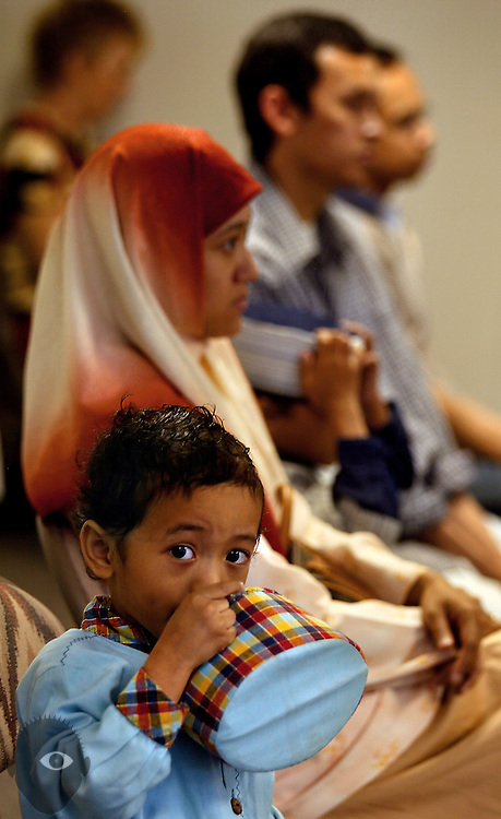 Tariq Ridha, 4, sits beside his mother Vanda and brother Fatih, 6, during a fellowship between Beaverton's Bilal Mosque and visiting Indionesian Muslims. .