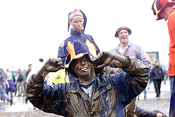 Festival fans enjoy themselves in the mud on Sunday, after heavy rain at the T in the Park music festival, held at Balado, Kinross in Fife, Scotland, on the weekend of Saturday 8 July and Sunday 9 July 2000..