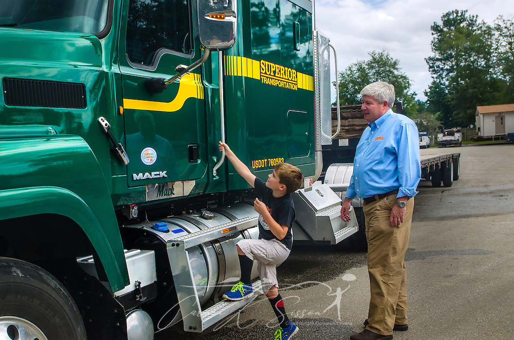 James Barber, 6, climbs onto a Mack truck as his father, Pat Barber, watches at Superior Transportation, Sept. 30, 2015, in North Charleston, South Carolina. Pat Barber started the company in 1998. James, 6, is already showing a big interest in the company and its Mack trucks, and Barber says he hopes he will follow in his footsteps and carry on the family legacy.  (Photo by Carmen K. Sisson/Cloudybright)