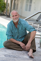 handsome middle aged man sitting by a hotel swimming pool in Fort Lauderdale, Florida