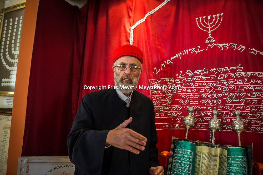 Mt Gerizim, Nablus, Palestine, March 2015. Husney W. Cohen, a priest and director of the Samaritan Museum on Mount Gerizim <br /> explains the Samaritan viewpoint about several biblical events. Samaritans believe the temple was to be built on Mount Gerizim rather than Jerusalem. They think Abraham offered Isaac on the mountain. They accept only the first five books (the Pentateuch) of the Old Testament. The Abraham Path is a long-distance walking trail across the Middle East which connects the sites visited by the patriarch Abraham. The trail passes through sites of Abrahamic history, varied landscapes, and a myriad of communities of different faiths and cultures, which reflect the rich diversity of the Middle East. Photo by Frits Meyst / MeystPhoto.com for AbrahamPath.org