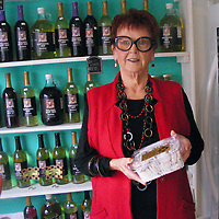 ALICE ORTIZ/BUY AT PHOTOS.MONROECOUNTYJOURNAL.COM<br /> Ann Tackett, owner of of 3 Goats Station in Aberdeen, holds a new item she has in the restaurant, Charleston Lemon Wafer Cookies. In the background are bottles of Mississippi muscadine juice. Most of the items in the restaurant are made in Mississippi, except for a few specialty items like the cookies.