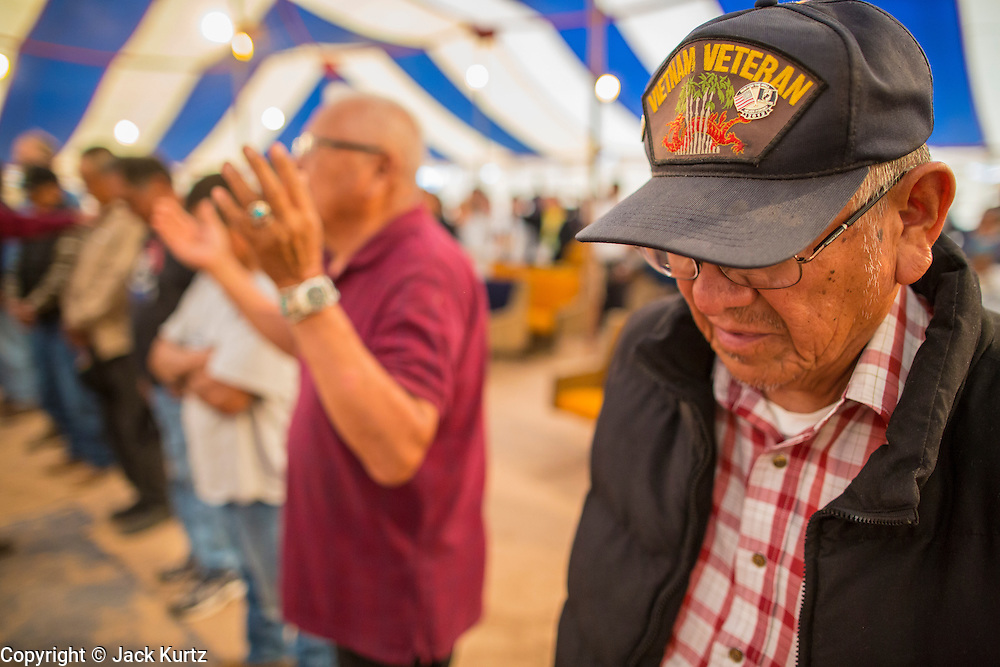 "13 JULY 2012 - FT DEFIANCE, AZ: Veterans line up for a special alter call during the veterans' service Friday night at the 23rd annual Navajo Nation Camp Meeting in Ft. Defiance, north of Window Rock, AZ, on the Navajo reservation. Preachers from across the Navajo Nation, and the western US, come to Navajo Nation Camp Meeting to preach an evangelical form of Christianity. Evangelical Christians make up a growing part of the reservation - there are now more than a hundred camp meetings and tent revivals on the reservation every year. The camp meeting in Ft. Defiance draws nearly 200 people each night of its six day run. Many of the attendees convert to evangelical Christianity from traditional Navajo beliefs, Catholicism or Mormonism. ""Camp meetings"" are a form of Protestant Christian religious services originating in Britain and once common in rural parts of the United States. People would travel a great distance to a particular site to camp out, listen to itinerant preachers, and pray. This suited the rural life, before cars and highways were common, because rural areas often lacked traditional churches.  PHOTO BY JACK KURTZ"