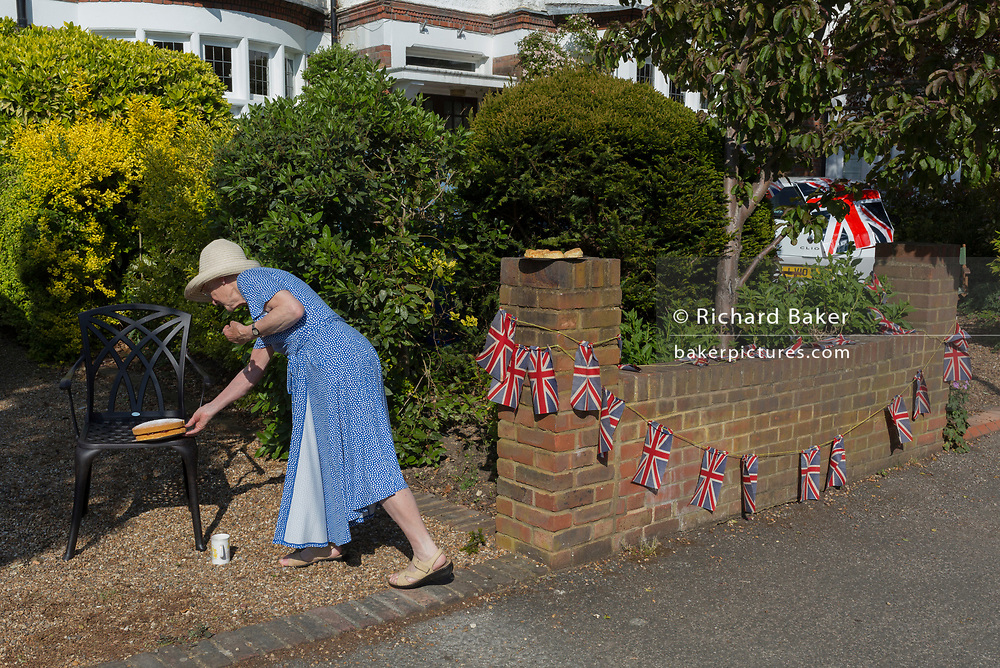 As the Coronavirus lockdown continues over the May Bank Holiday, the nation commemorates the 75th anniversary of VE Day (Victory in Europe Day, the day that Germany officially surrendered in 1945) and in Dulwich, neighbours and residents emerge from their homes to party while still observing social distancing rules. A local lady resident shares home-made cake to neighbours, on 8th May 2020, in London, England.