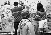 People writing messages on a wall. Glastonbury 2008