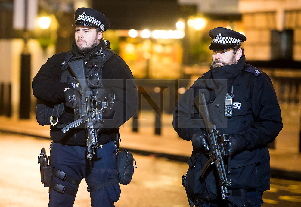 © Licensed to London News Pictures. 31/12/2015. London, UK. Armed police watch over revellers in Westminster, central London toady (Thurs) as security in the capital is heightened ahead of New Year celebrations this evening.  Photo credit: Ben Cawthra/LNP