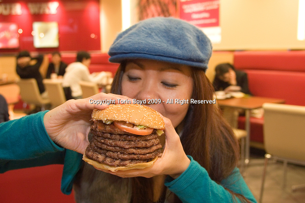 """This is the """"Windows 7 Whopper"""", a seven layer beef patty hamburger being sold for a limited time only at all Burger King outlets in Japan. This is a special campaign to commemorate the release of Windows® 7, Microsoft's new operating system. Both the hamburger and operating systems were released on October 22, 2009, and according Burger King Japan (BKJ) the idea for this promotional campaign originated by Microsoft. As for sales of this mega burger in a land where fresh fish and healthy diets are the norm, the Windows 7 Whopper has been a huge success. So much that the campaign has been extended an additional week to November 6, 2009. To date, October 31, a total of 10,000 Windows 7 Whoppers have sold, more than doubling their original sales forecast of 4500 by this same date. The price of the burger is 1,450 yen or $16 USD (including tax), but they also offer the first 30 burgers at each outlet daily for 777 yen $8.60 USD. These first 30 quickly sell out with most customers lining up outside prior to opening hours to purchase the discounted burger. This Windows 7 Whopper campaign is only taking place in Japan where Burger King opertates fifteen outlets nationwide (and growing). The woman in the photo is Eri Hiraoka of Tokyo, sampling a Windows 7 Whopper at the Nishi Shinjuku Burger King outlet in Tokyo on October, 31, 2009...Nutritional facts: each Windows 7 Whopper contains 7 layers of beef patties and contains 2120 calories. It weighs a 950 grams (2.09 lbs), or nearly one kilo. As for fat content, a normal single patty Whopper contains 40 grams of fat, so the estimated fat content of the Windows 7 Whopper is an astounding 280 grams of fat, the same as  2.5 sticks of butter. The daily recommended fat intake for most is 30-35 grams of fat per day."""
