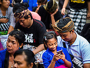 13 JULY 2016 - UBUD, BALI, INDONESIA:  A girl sits in her father's lap while she plays games on her smart phone at a mass cremation in Ubud. Local people in Ubud exhumed the remains of family members and burned their remains in a mass cremation ceremony Wednesday. Almost 100 people will be cremated and laid to rest in the largest mass cremation in Bali in years this week. Most of the people on Bali are Hindus. Traditional cremations in Bali are very expensive, so communities usually hold one mass cremation approximately every five years. The cremation in Ubud will conclude Saturday, with a large community ceremony.     PHOTO BY JACK KURTZ