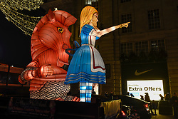 © Licensed to London News Pictures. 23/11/2018. LONDON, UK. A vehicle carrying an illuminated Alice in Wonderland passes signs advertising Black Friday on display near Piccadilly Circus.   Traditional retailers face increasing challenges to attract customers against their online competition.  Photo credit: Stephen Chung/LNP