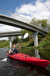 North America, United States, Washington, Bellevue, teenage boy kayaking under highway bridge in Mercer Slough Nature Park.  MR