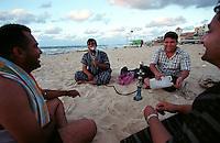 Men smoke from a hookah on the beach in Gaza City. (Photo/Scott Dalton)