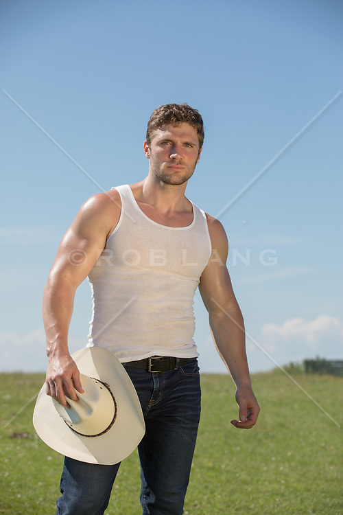 cowboy in a tank top holding his hat