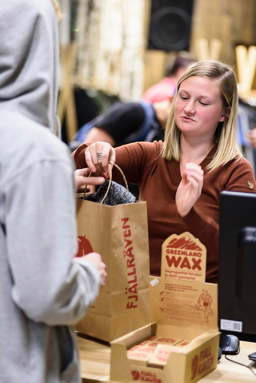 Guests mingle and look at clothing apparel and outdoor-outfitter gear during a grand opening event for Fjällräven Madison, a Swedish-heritage brand store in downtown Madison, Wis., on Oct. 22, 2015. Pictured is Victoria Albrecht, assistant manager of the Fjällräven Madison Store. (Photo by Jeff Miller - www.jeffmillerphotography.com)