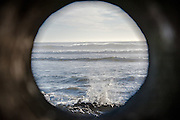View through a peep hole to the ocean in the tunnel at Oceanside Beach