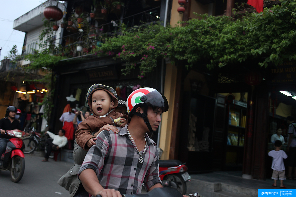 A street scene as a family ride past on a scooter in Hoi An, Vietnam. Hoi An is an ancient town and an exceptionally well-preserved example of a South-East Asian trading port dating from the 15th century. Hoi An is now a major tourist attraction because of its history. Hoi An, Vietnam. 5th March 2012. Photo Tim Clayton