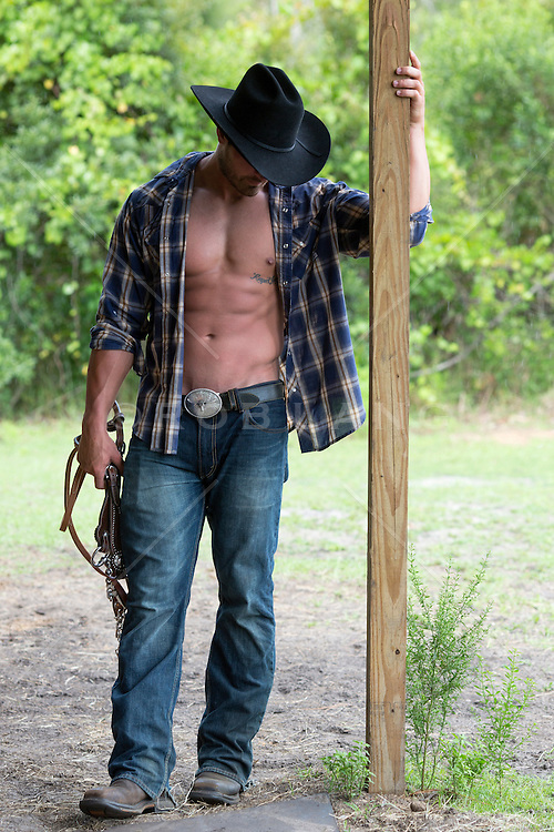 cowboy with an open shirt holding on to a wooden post
