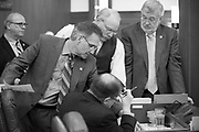 "From right Sen. Gary Stevens (R), Sen. Bert Stedman (R), Sen. Kevin Meyer (R) lean over Sen. Lyman Hoffman's desk during an ""at ease"" on the Senate Floor Sunday."