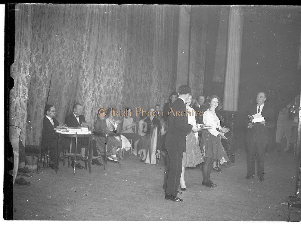 07/11/1959<br /> 11/07/1959<br /> 07 November 1959<br /> All Ireland Final of Gael Linn Children's Singing Competition at Francis  Xavier Hall, Dublin. Picture shows Diarmuid O Broin, Director of the Competition, congratulating the two Cork entrants. Aine Ní Rinn of Millstreet Cork (right), who won 1st prize and Maire Ní Dhoibhlinn of Cork City who won 2nd place. On right is Proinsias Ó Ceallaigh.