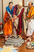 The bride and groom at an Indian wedding making offerings of puffed rice to the holy fire accompanied by the priest.