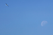 A glider share the sky with the waning moon, lower right, above Wurstboro Airport on Sunday, Sept. 18, 2011.