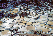 "Since pre-Inca times, salt farmers at the saltworks (salinas) near Maras have evaporated salty water from a subterranean stream in Peru, South America. A rough dirt road connects Maras (in the Urubamba/Vilcanota River Valley, Sacred Valley of the Incas) with Cuzco (40 km north) and other towns. The cooperative system of pond farmers was established during the time of the Incas, if not earlier, and is traditionally available to any person wishing to harvest salt. Intricate channels redirect water flow through several hundred ancient terraced ponds. As water evaporates from the sun-warmed ponds, it becomes supersaturated and salt precipitates as crystals. A pond keeper closes the water-feeder notch, allows the pond to go dry, then scrapes and carries away the dry salt. Salt color varies from white to a light reddish or brownish tan, depending on ""farmer"" skills."