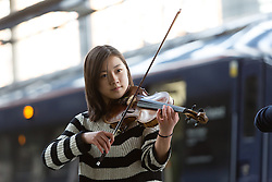 © Licensed to London News Pictures. 01/03/2016. London, UK. Two exceptional teenage violin prodigies, Coco Tomita, 13 and Louisa Staples, 15, (not pictured) who are competitors in the world's leading competition for young violinists, the Menuhin Competition London 2016 (which takes place on 7-17 April 2016), surprise commuters as they perform on the platform at St Pancras International Station in London. Photo credit : Vickie Flores/LNP
